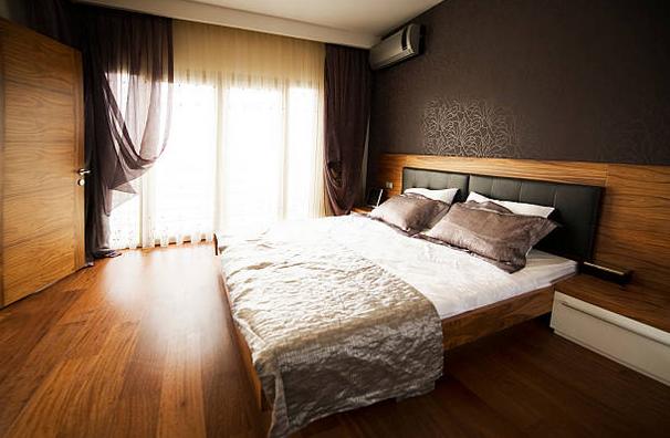 Chambre d'adulte avec parquet en bois sombre et murs marrons